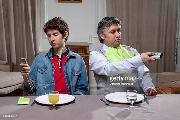 Father and son, distracted at the dinner table