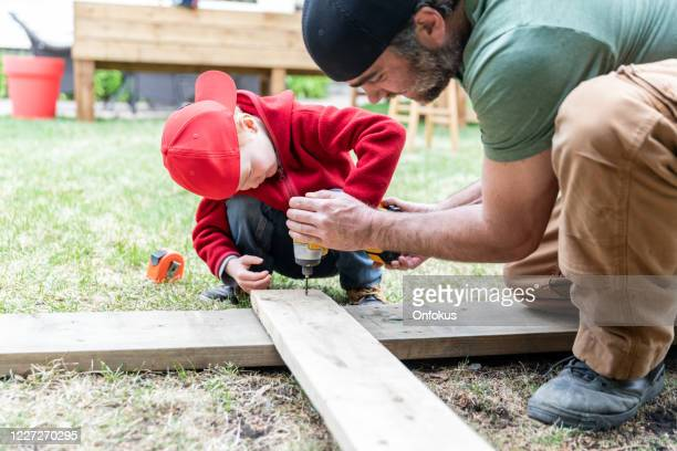 father and son doing a construction project while in quarantine - council flat stock pictures, royalty-free photos & images