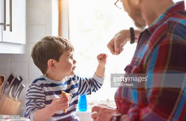 father and son doing a fist bump - fist bump stock pictures, royalty-free photos & images