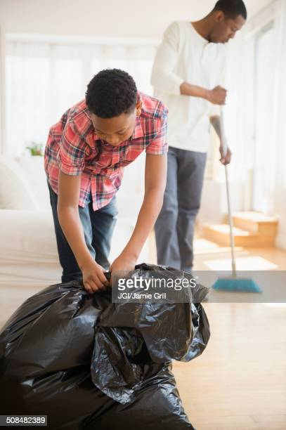 father and son doing chores in house - sweeping stock pictures, royalty-free photos & images