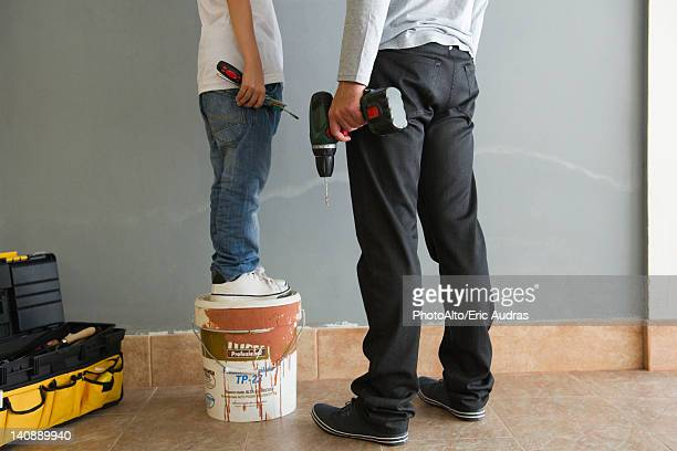 Father and son doing home improvement, low section