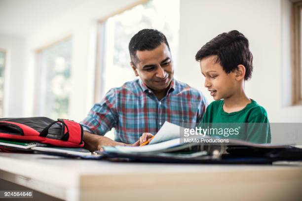 father and son doing homework at home - homeschool ストックフォトと画像