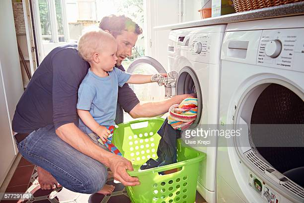 father and son doing laundry together - appliance fotografías e imágenes de stock
