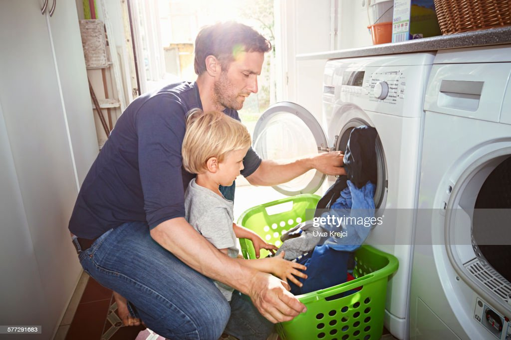 Father and son doing laundry together : Stock Photo
