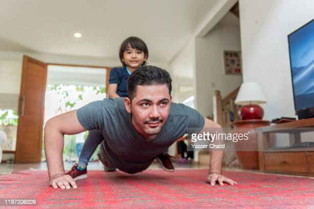 father and son doing push up on a living room - wellness stock pictures, royalty-free photos & images