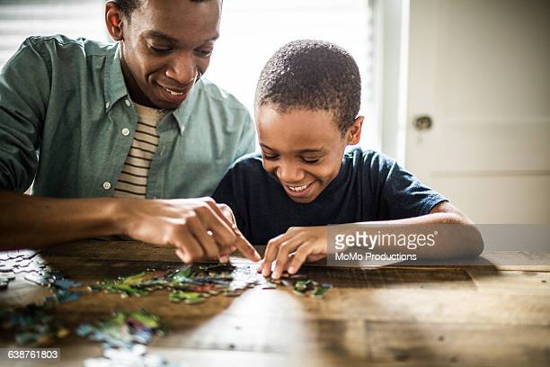 father and son doing puzzle - puzzle stock pictures, royalty-free photos & images