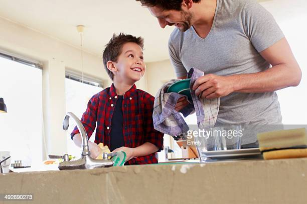 Father and son doing washing up
