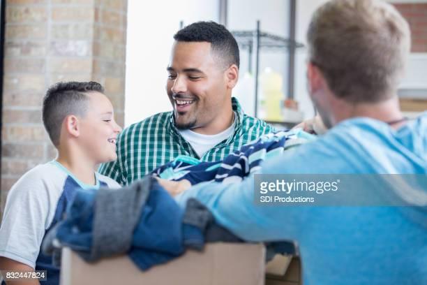 pai e filho doam roupas para abrigo - casaco - fotografias e filmes do acervo