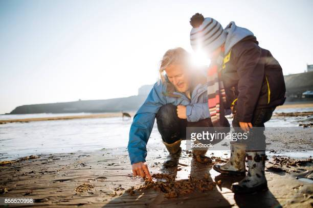 Père et fils de dessin dans le sable sur une journée d'hiver