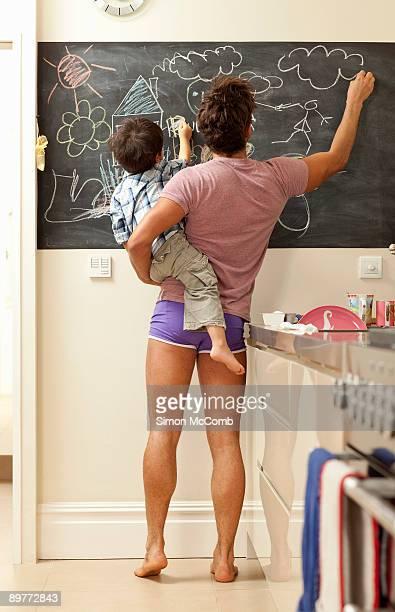 father and son drawing on chalkboard - bambini in mutande foto e immagini stock