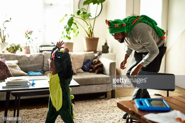father and son dressed as dragons playing in living room - spelen stockfoto's en -beelden