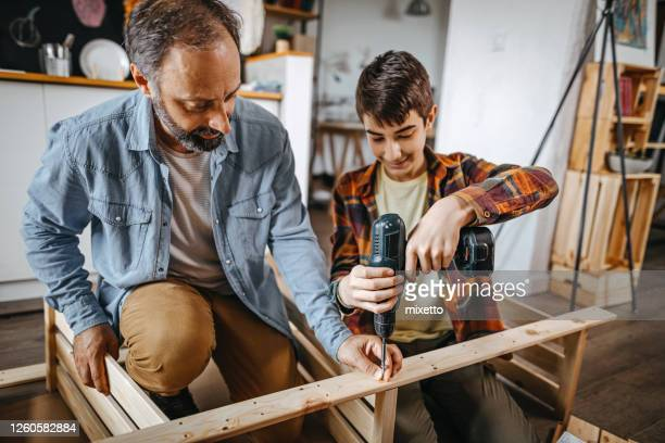 tablón de perforación de padre e hijo en casa - taladro fotografías e imágenes de stock