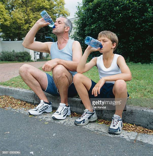 father and son drinking water - thirsty stock pictures, royalty-free photos & images