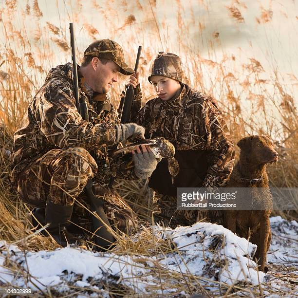 father and son duck hunting with their dog