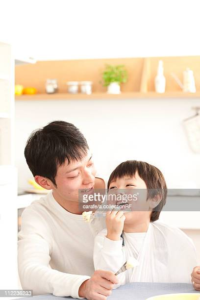 Father and son eating apple