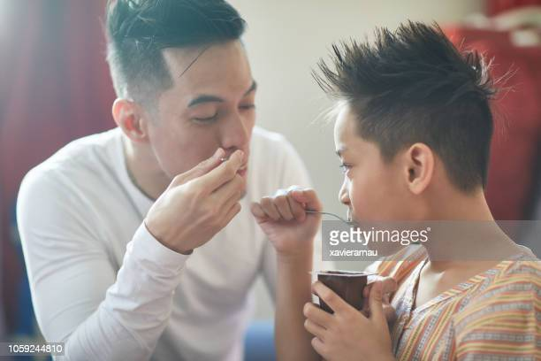 father and son eating breakfast at home - filipino family eating stock pictures, royalty-free photos & images