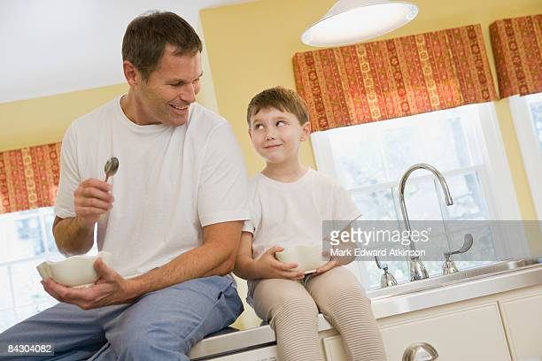 Father and son eating breakfast on kitchen counter