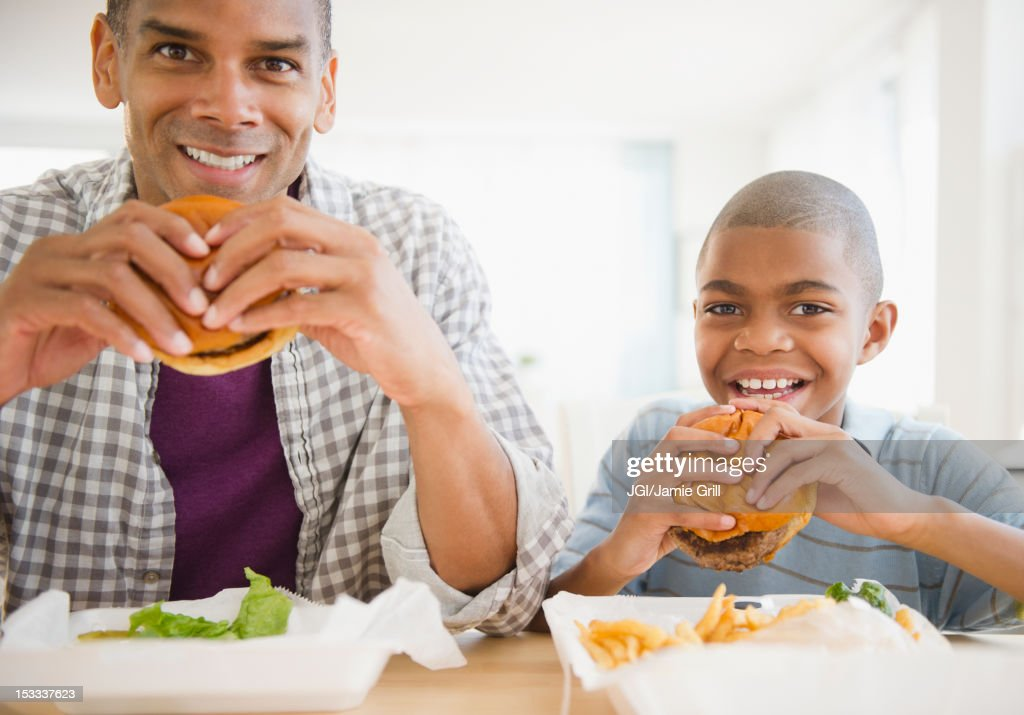 Father and son eating hamburgers : Stock Photo