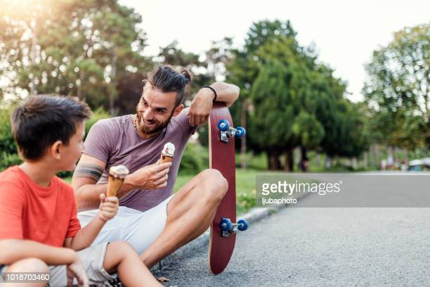 Father and son eating ice cream in public park