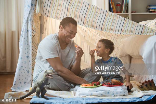 Father and son eating in blanket fort