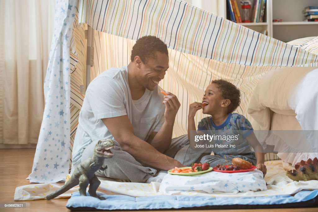Father and son eating in blanket fort : Stock Photo