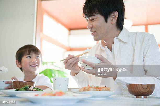 Father and son eating Japanese breakfast, smiling