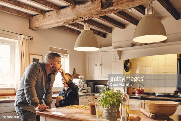 father and son eating pizza in kitchen at home - dean foods stock photos and pictures