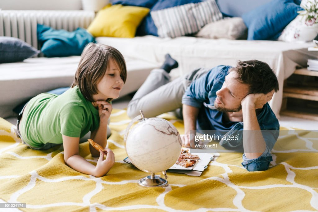 Father and son eating pizza next to globe on the floor at home : Stock Photo