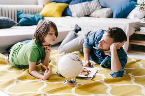 Father and son eating pizza next to globe on the floor at home - gettyimageskorea