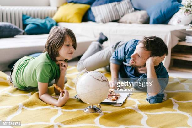 father and son eating pizza next to globe on the floor at home - world kindness day fotografías e imágenes de stock