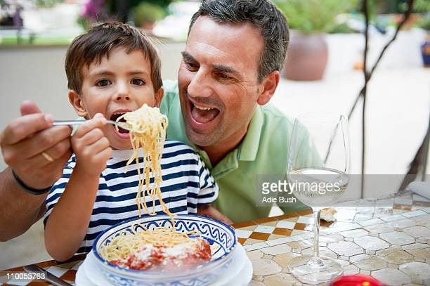 Father and son eating spaghetti