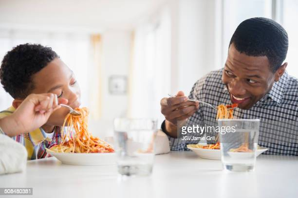 father and son eating together at table - black family dinner stock photos and pictures