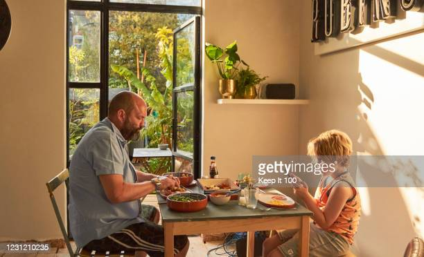 father and son eating together - vegetarian food stock pictures, royalty-free photos & images