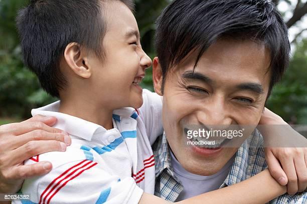 Vater und Sohn (7 und 9), umarmen und Lachen im park