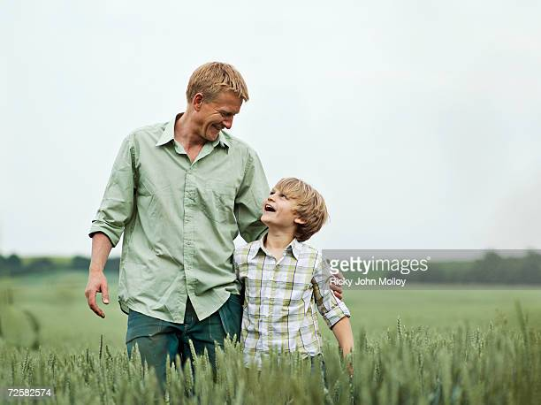Father and son (8-9) embracing in field