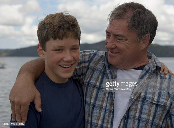 Father and son (12-14) embracing, outdoors, son smiling, portrait