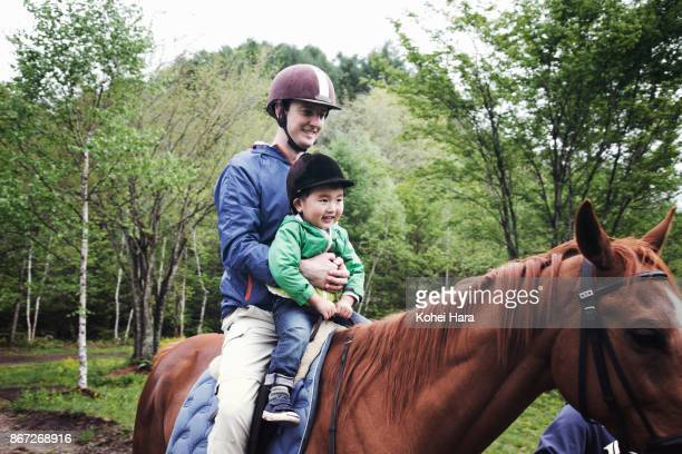 father and son enjoying a horse riding together in the ranch in the rain - gunma prefecture stock photos and pictures