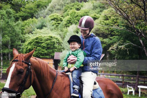Father and son enjoying a horse riding together in the ranch in the rain