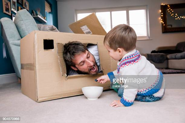 Father and Son enjoying a snack whilst playing at home with a cardboard box