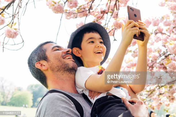 father and son enjoying cherry blossom - hanami stock pictures, royalty-free photos & images