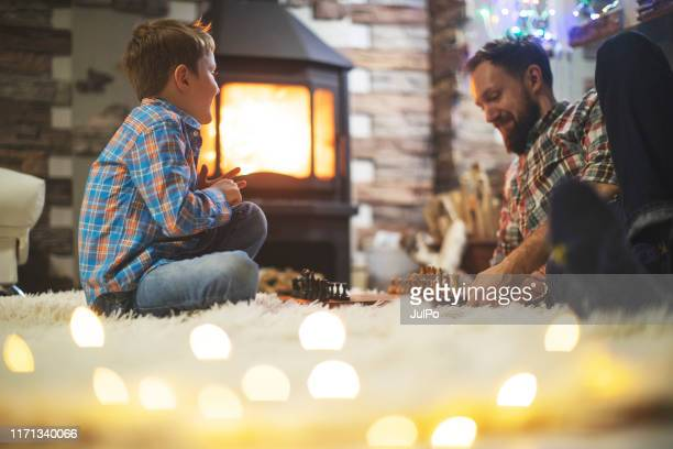 father and son enjoying christmas holidays at home - board game stock pictures, royalty-free photos & images