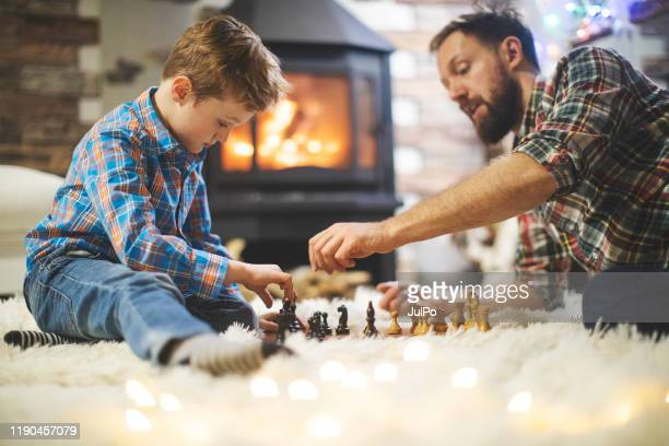 father and son enjoying christmas holidays at home - game night leisure activity stock pictures, royalty-free photos & images