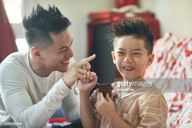 father and son enjoying eating breakfast at home - filipino family eating stock pictures, royalty-free photos & images