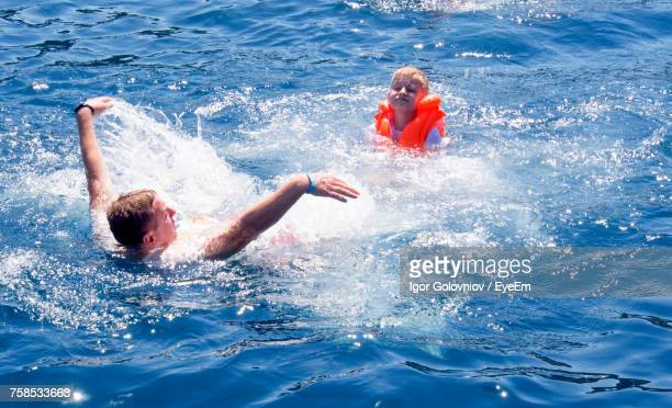 father and son enjoying in sea during sunny day - igor golovniov stock pictures, royalty-free photos & images