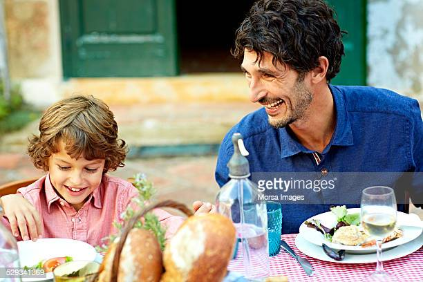 Father and son enjoying meal at outdoor table