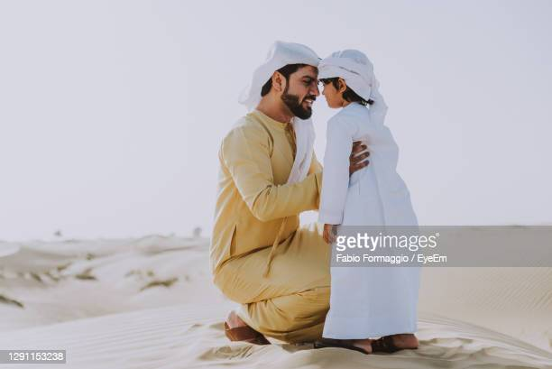 father and son enjoying while crouching in desert - dubai stock pictures, royalty-free photos & images