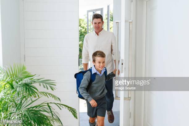 father and son entering main door of house - entering stock pictures, royalty-free photos & images