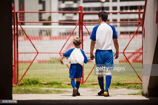 father and son entering soccer stadium - trikot stock-fotos und bilder