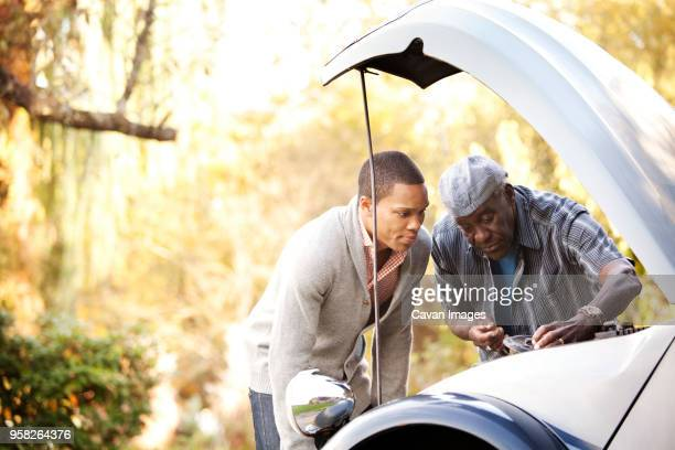 Father and son examining car engine