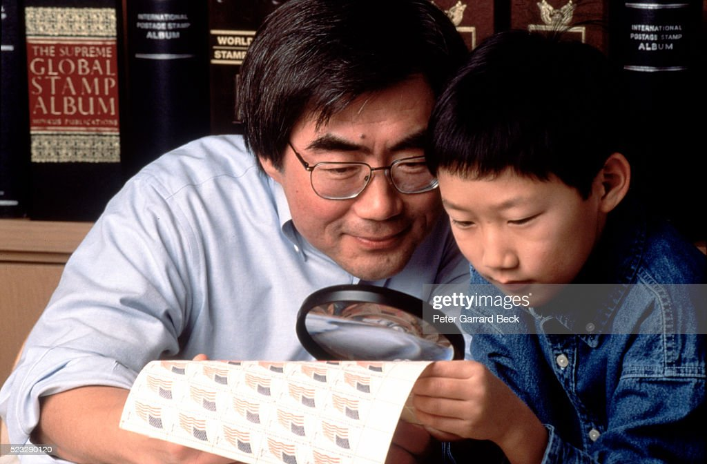 Father and Son Examining Stamps : Stock Photo